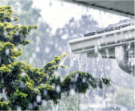 Image of the corner of a roof of a house during a rainstorm with water splashing out of a gutter
