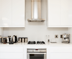 Image of a stove and various stainless steel appliances in a white kitchen
