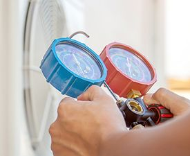 A person's hands using a tool to check an air conditioning unit outdoors