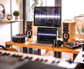A desk with a laptop, a monitor, speakers and other music equipment