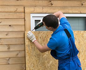man drilling plywood over window