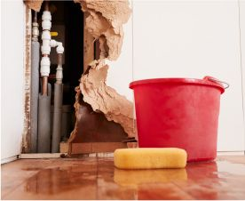 Image of a damaged wall with water a sponge and a bucket on the ground