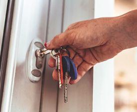 A woman's hand using keys to unlock her front door
