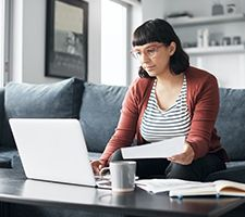 A young woman sitting on a couch looking at her laptop and a piece of paper