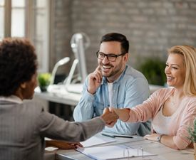 A woman and a man sit across a desk from another woman The two women are shaking hands