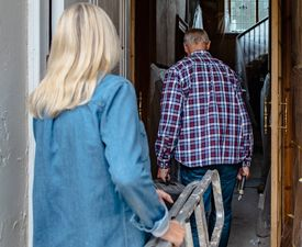 Image of an older man and woman carrying a ladder into a house