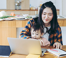 A mom and child using a laptop at the kitchen table
