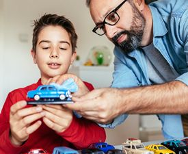 A father and son playing with a toy car in a kids room