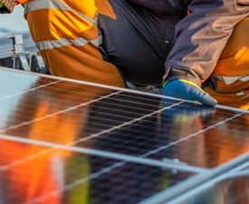 Person in construction gear working on a solar panel on a roof